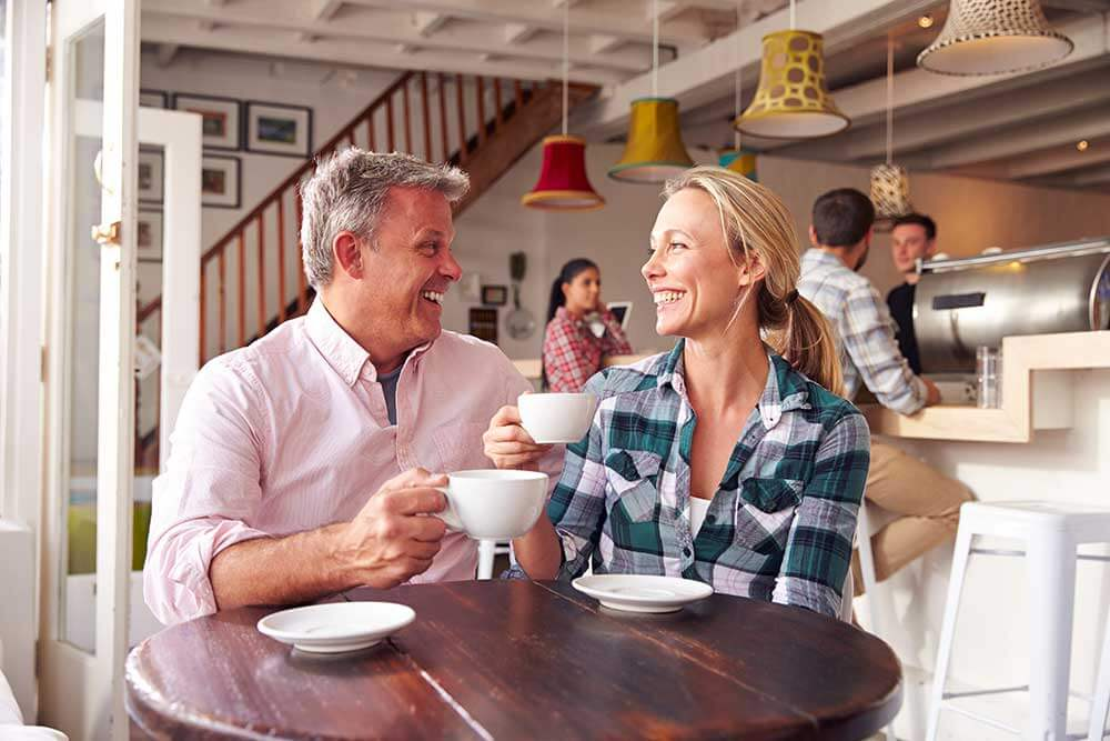 A man and woman are on a date at a coffee shop. They're smiles are beautiful thanks to restorative dentistry.