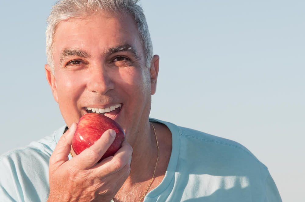 A man is eating an apple. He has stunning teeth from visiting his dentist.