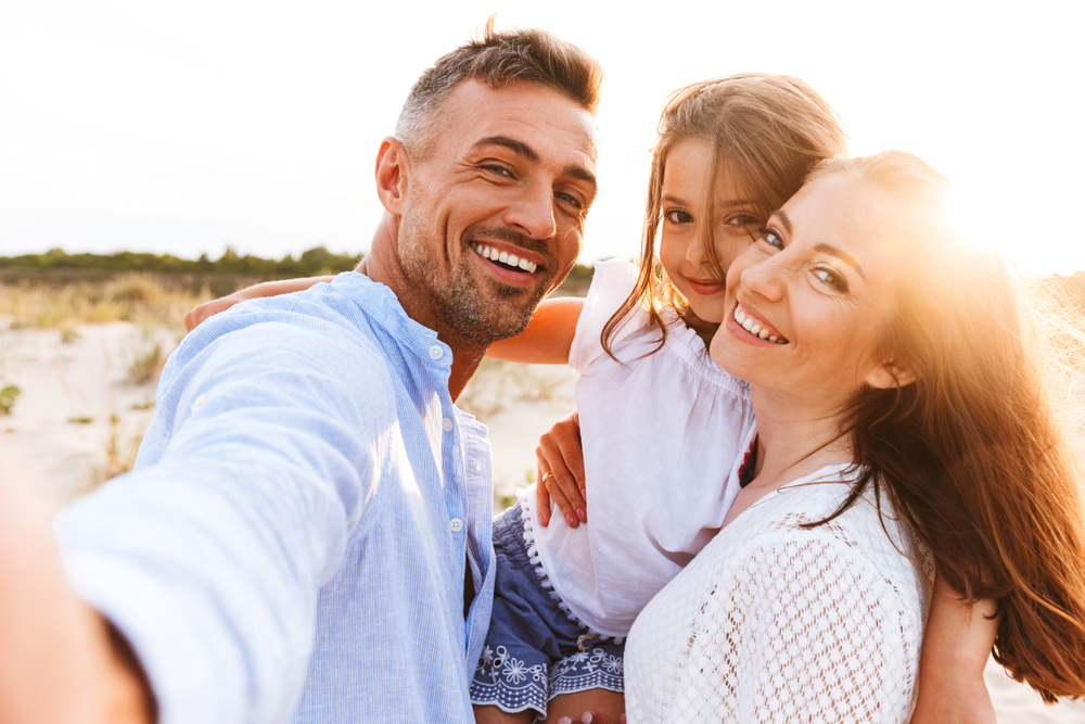 A family is on the beach and smiling proudly thanks to restorative dentistry.