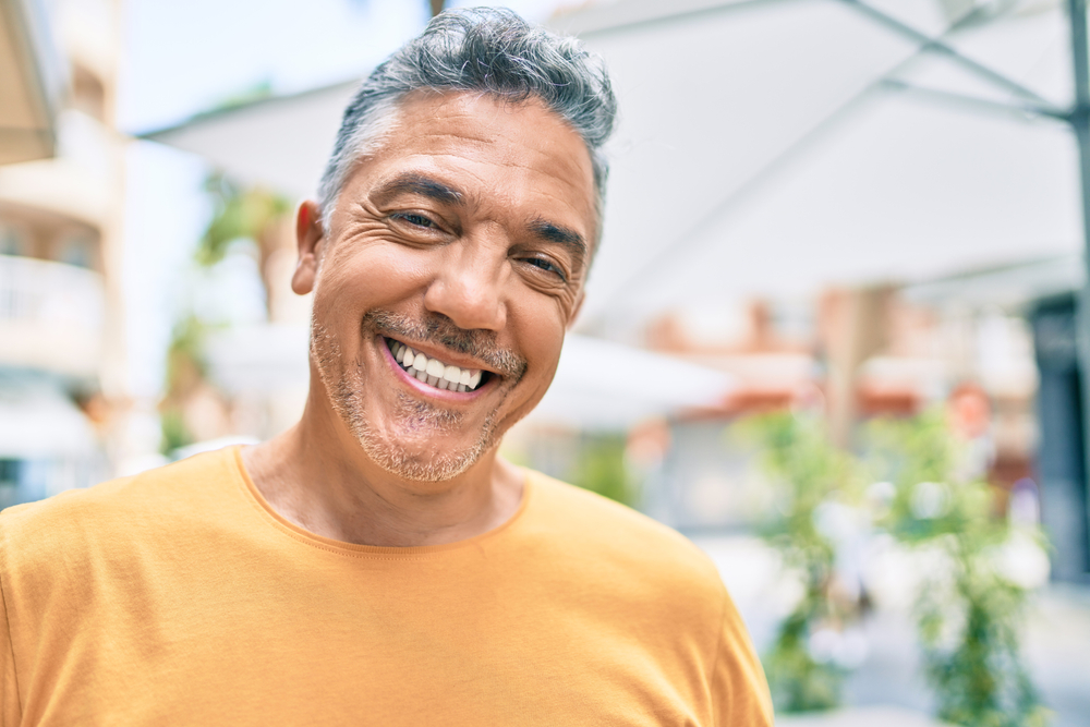 A man is smiling following his periodontics treatment.