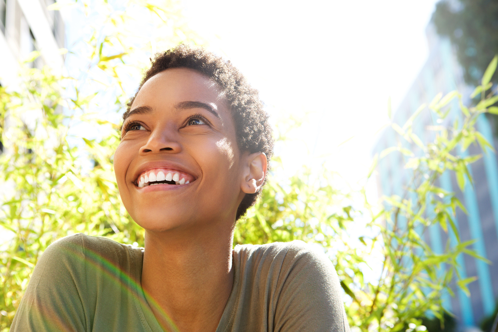 A woman is smiling about the results of her cosmetic dentistry procedure.