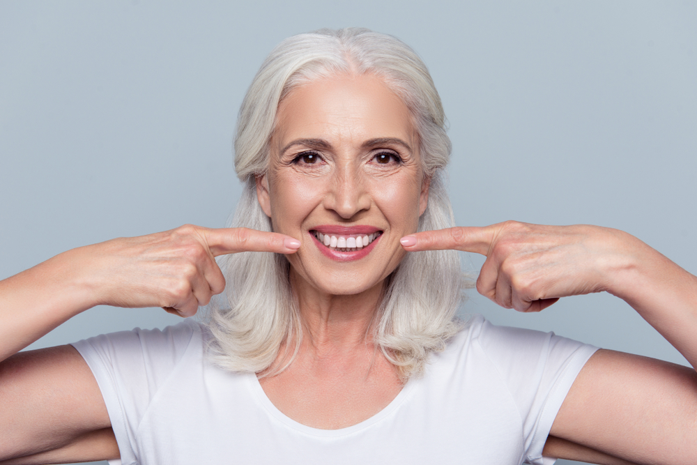 A woman points to her dental implants and smiles.