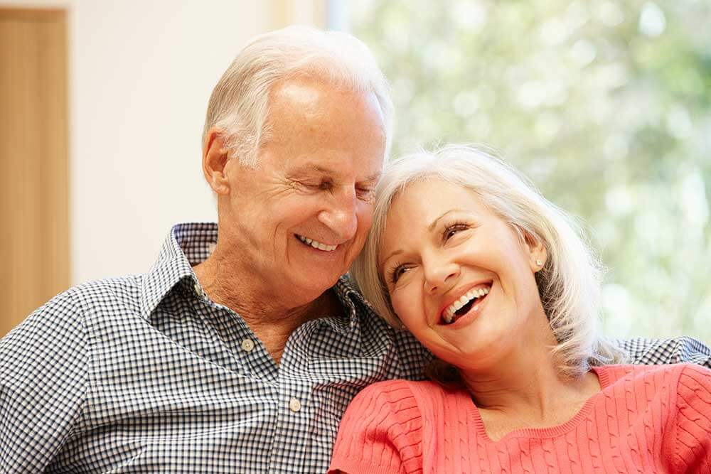 An older couple is smiling and leaning on each other. Their restorative dentistry looks beautiful.