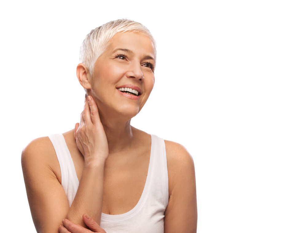 A woman places a hand on her neck and smiles. She's wearing white and has white hair and white restorative dentistry.