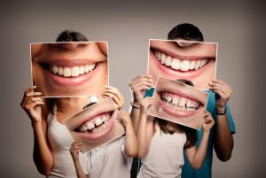 A family holds up photos of their smiles maintained by expert general dentistry.