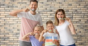 A family is practicing at-home general dentistry by brushing their teeth.