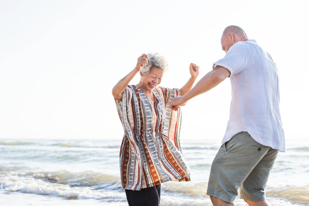 A man and woman visit the beach after their dental appointment. They're dancing and not in pain.