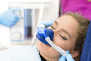 A woman with winged eyeliner is being sedated for her general dentistry appointment.